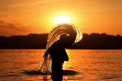 Beautiful silhouette of young girl at summer sunset in water Stock Images
