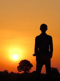 Beautiful silhouette of young Man at sunset time with sun and tree in background Royalty Free Stock Photo