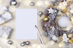 Christmas wreath, notebook and presents. Beautiful silver Christmas wreath decorated with candle, cones, stars and baubles, notebook with pen for writing and royalty free stock image
