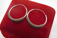 Feminine jewelry - silver earrings in the shape of circles stock photography