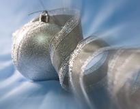 Beautiful silvery New Year ball and elegant tinsel Stock Photo