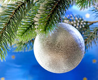 Beautiful silvery New Year's ball on a branch of a Christmas tree.close up on a blue background Royalty Free Stock Images