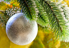 Beautiful silvery New Year's ball on a branch of a Christmas tree on a yellow background Stock Photography