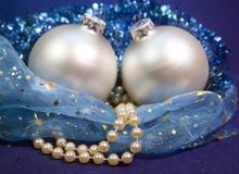 Beautiful silvery New Year`s ball, brilliant tinsel and a pearl beads on a blue background - New Year`s composition, a card.  Stock Photo