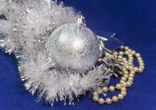 Beautiful silvery New Year`s ball, brilliant tinsel and silver cones on a blue background - New Year`s composition. A card Stock Image