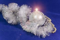 Beautiful silvery New Year`s ball, brilliant tinsel and silver cones on a blue background - New Year`s composition, a card.  Stock Photography