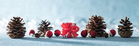 Beautiful simple Christmas banner with copy space. Cute Christmas present, red ornaments and pine cones on shiny blue background. Beautiful simple Christmas stock image