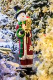 Beautiful simple figurine of snowman in Santa�Claus outfit among glowing Christmas trees with lights. Beautiful simple figurine of snowman in Santa� royalty free stock image