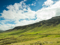 Beautiful simple landscape with green field and mountains. Royalty Free Stock Image