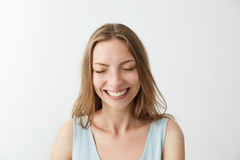 Beautiful sincere happy cheerful girl smiling laughing with closed eyes over white background. Stock Image