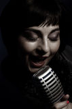Beautiful singer. Singing with a retro microphone Stock Photography