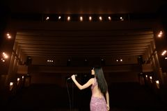 Beautiful singer against the auditorium. Back view girl in long gown performing on stage stock photos