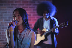 Beautiful singer with guitarist performing in nightclub. Beautiful female singer with male guitarist performing in nightclub Royalty Free Stock Photography