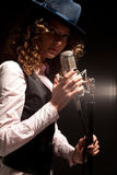 Beautiful singer in hat with microphone Stock Image