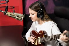 Beautiful singer playing guitar in radio station. Cute young female singer wearing headphones recording and playing guitar in radio station royalty free stock photo
