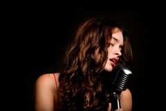 Beautiful singer singing with microphone Stock Image
