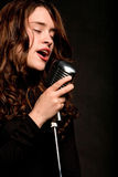 Beautiful singer singing with microphone Royalty Free Stock Images