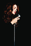 Beautiful singer singing with microphone Stock Images