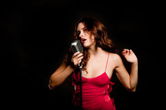 Beautiful singer singing with microphone Stock Photos