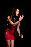 Beautiful singer singing with microphone Royalty Free Stock Photo