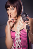 Beautiful singer singing with a retro microphone Royalty Free Stock Photo