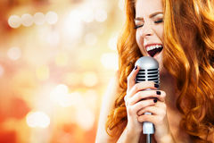 Beautiful Singing Girl. Beauty Woman with Microphone. Glamor fashion Woman with Microphone over Blinking bokeh night background royalty free stock images