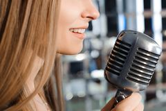Beautiful Singing Girl. Beauty Woman with Microphone. Glamour Model Singer. Karaoke song. stock photo