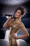 Beautiful singing girl. Beauty woman with microphone. Glamour model singer. Karaoke song royalty free stock image