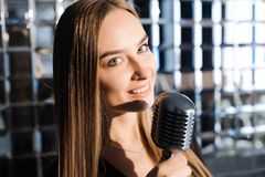 Beautiful Singing Girl. Beauty Woman with Microphone. Glamour Model Singer. Karaoke song.  stock photography