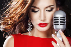 Beautiful Singing Girl. Beauty Woman in red dress with Microphone stock photos