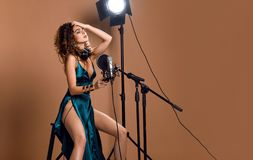 Beautiful singing girl curly afro hairstyle. Beauty woman singer sing with microphone karaoke song in modern green emerald dress. Beautiful singing girl curly royalty free stock images