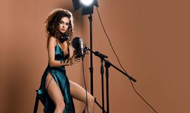 Beautiful singing girl curly afro hairstyle. Beauty woman singer sing with microphone karaoke song in modern green emerald dress. Beautiful singing girl curly stock photos
