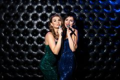 Beautiful Singing Girls With Microphone Karaoke Song On Stage On Dark Background Royalty Free Stock Photo