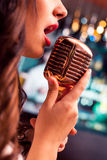 Beautiful Singing Glamour Model Singer. Karaoke song. Beautiful Singing Girl. Beauty Woman with Microphone over Blinking bokeh night background. Glamour Model Royalty Free Stock Images