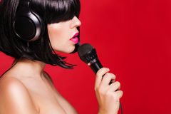 Beautiful singing woman with microphone. Singer. Royalty Free Stock Image