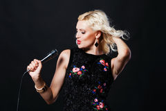 Beautiful singing woman with microphone. Singer. Royalty Free Stock Photo