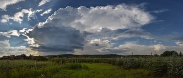 Panoramic view of an isolated thunderstorm with elongated anvil over the countryside of Transylvania, Romania. royalty free stock image