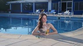 Beautiful single woman enjoying relax, drinking in swimming pool. Stock footage stock video footage