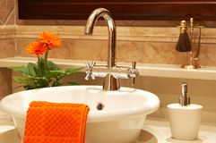 Beautiful sink in a bathroom. With towel on it and a flower. Focus is on the tap Royalty Free Stock Photos