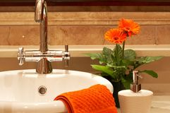 Beautiful sink in a bathroom. With towel on it and a flower. Focus is on the tap Stock Images