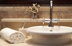 Beautiful sink in a bathroom. With rolled up towel next to it and flowers Royalty Free Stock Photo