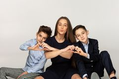 Beautiful sister sitting on the ground with two younger brothers royalty free stock photography