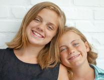 Beautiful sisters in affectionate pose. A thirteen year-old teenage girl and her ten year-old sister are posing against a white brick wall. They have their heads royalty free stock photo