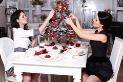 Beautiful sisters decorating Christmas tree at home Stock Photos