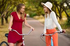 Beautiful sisters riding bicycles in park. Beautiful sisters in fashion outfits riding bicycles in park in summer Royalty Free Stock Image