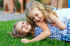 Beautiful sisters having fun on green field. Beautiful laughing girls sisters having fun playing on green field Stock Photo