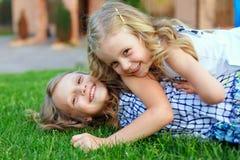 Beautiful sisters having fun on green field Stock Photo