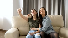 Beautiful sisters in the living room on the couch taking a selfie. They are having fun, laughing and smiling and spending quality time together stock video footage