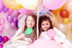 Beautiful sisters with lollipops posing at camera Stock Images