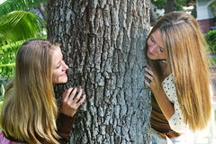 Beautiful Sisters Playing Outdoors. Beautiful teenage sisters playing outdoors, peeking around a tree Royalty Free Stock Images